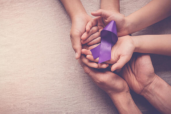 Adult and child hands holding purple ribbon, symbolizing domestic violence awareness.