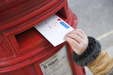 Posting a postcard in a old school red mailbox.