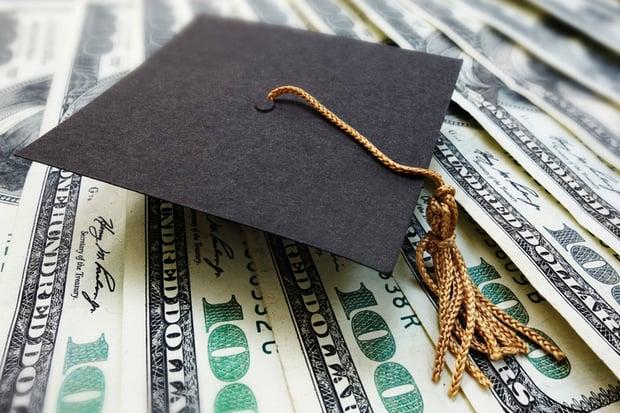Mini graduation mortar board cap on money.