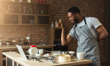 Man seasoning food at home kitchen having fun, while video-chatting his date.