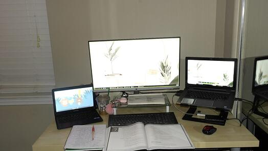 A desk set up of monitors and computers and papers.