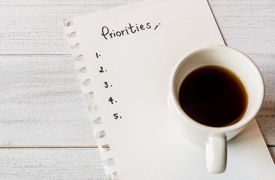 A cup of coffee next to a priorities list; for the Prioritize section