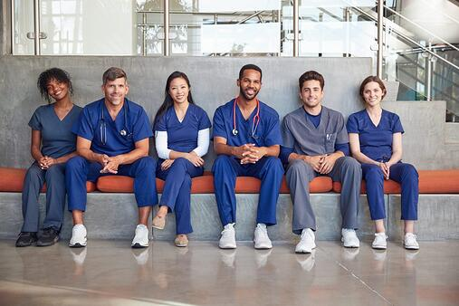 A diverse group of doctors and nurses smile at the camera on their break.