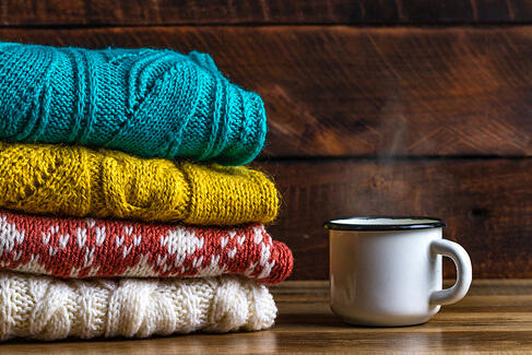 A pile of fun and funky sweaters next to a steaming mug of cocoa