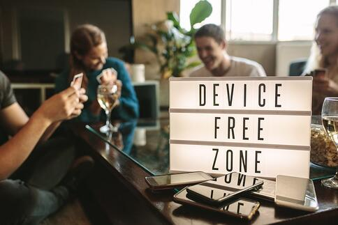 """Some young people play cards together in front of a sign that reads """"Device Free Zone."""" Their phones are stacked in front of the sign."""