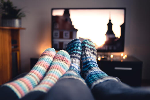 A couples' feet, both clothed in woolen socks, in front of a TV as a movie starts.