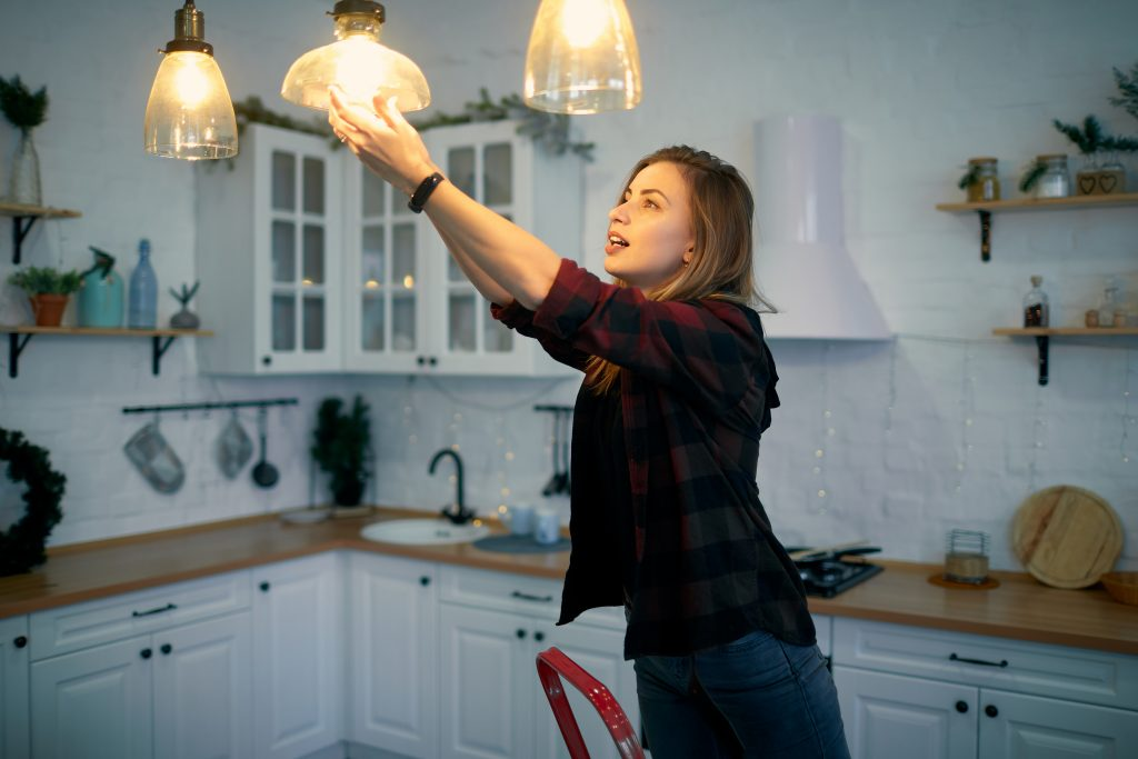 A young woman changes the light bulbs.