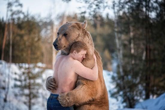 A man with no shirt hugs a bear, who hugs gently back.