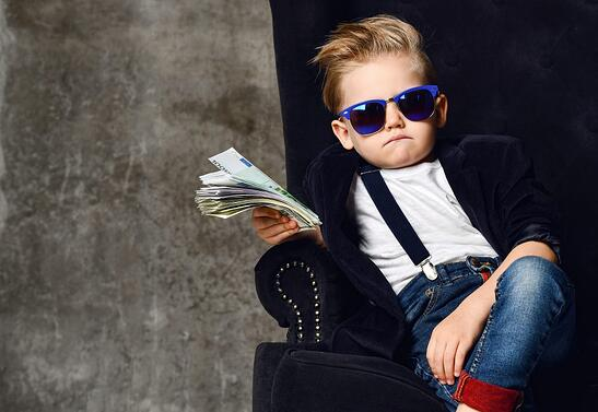 A toddler wearing a little suit and blue sunglasses with a pile of cash in hand.