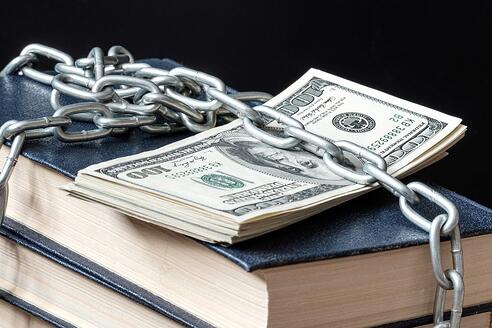 Hundred dollar bills chained to a set of books.