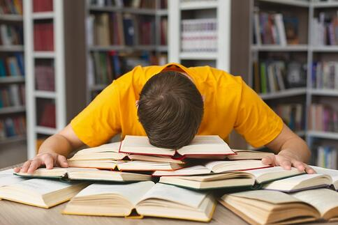 A college student rests his head on ginormous pile of books, too tired to study.
