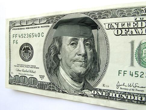 A 100 dollar bill with ben franklin wearing a graduation cap.