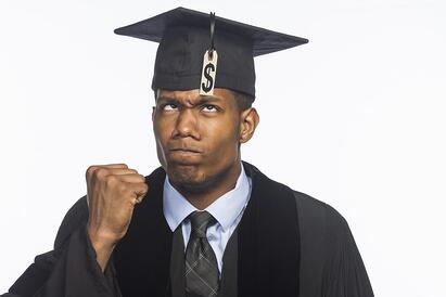 A young man pumps his fist while wearing a graduation robe and cap; the cap has a dollar sign on it.