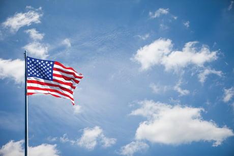 American flag waving in sunny daylight.