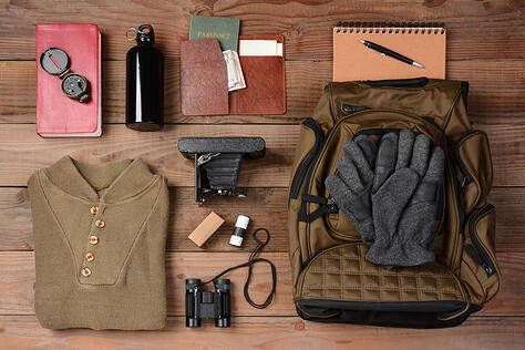 A bunch of travel gear, compass, backpack, sweatshirt, notebook, wallet, gloves, are laid out on a wooden table.