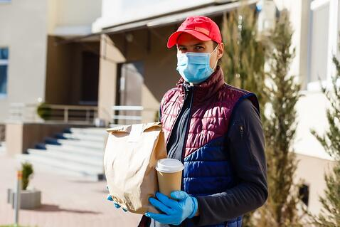 A delivery driver wearing a mask gets ready to deliver food.