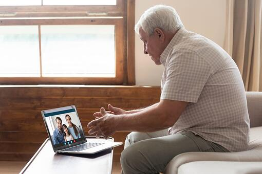 A wife, husband, and daughter video chat with a grandpa