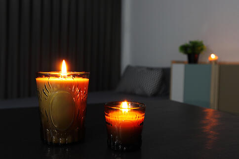 A pair of scented candles in a dimly lit room.