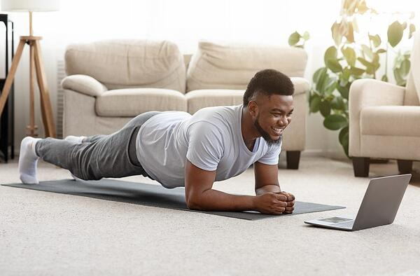Goes with Exercise section; an attractive man performs planks.