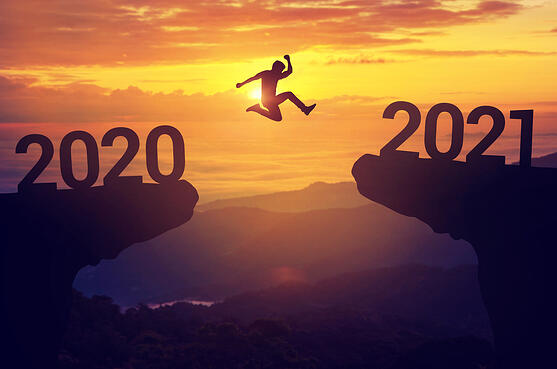 A man leaps from 2020 to 2021 on a mountainside