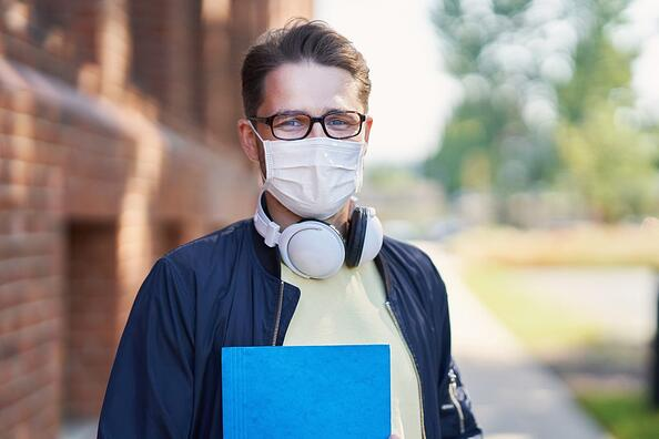 A man wearing a mask prepares to go back to college as an adult.