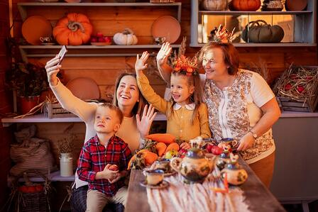 A family waves at someone on FaceTime on a phone, observing a safe Thanksgiving