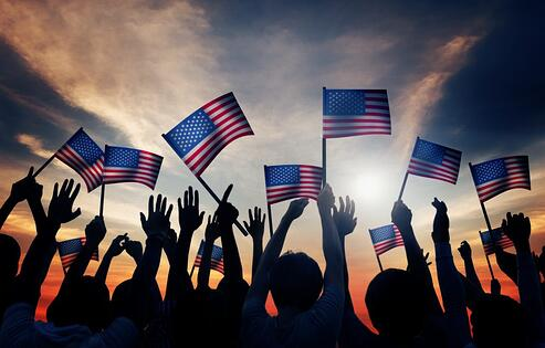 Group of people waving mini US flags during golden hour.