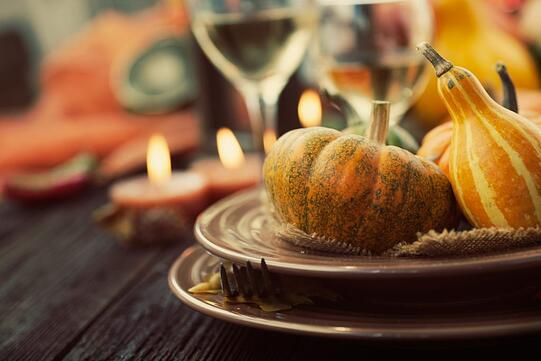 A thanksgiving place setting with wine and decorative pumpkins