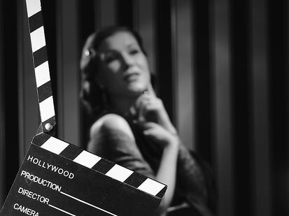 An old Hollywood black and white style photo of a lady in a dress, with a clapperboard in front.