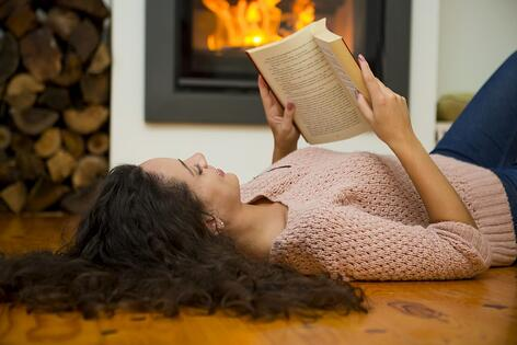 A woman reads a history book by a fireplace.