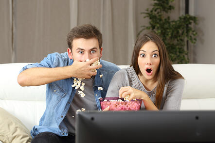 A boyfriend shovels popcorn into his mouth while a girlfriend watches open mouthed at a movie scene.
