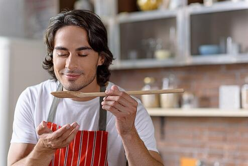 A men smells his spatula as he cooks.