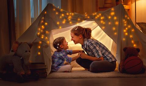 A mom and daughter play in an indoor makeshift tent at night.
