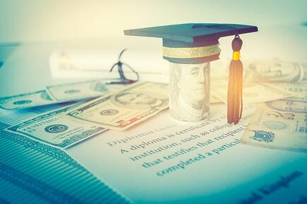 A 100 dollar bill is crowned with a graduation cap; it sits on top of a diploma.