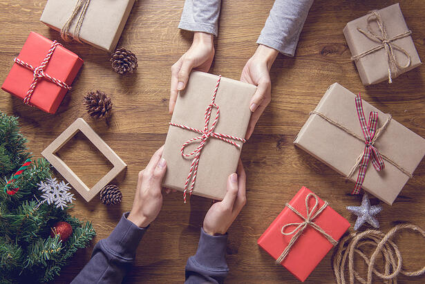 A woman hands a gift wrapped gift to a man for the holidays.