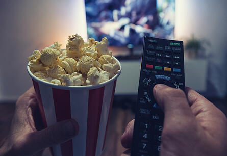 Two hands hold a bowl of popcorn and a TV remote, ready for a movie to start.