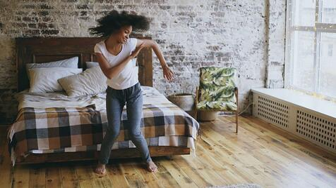 A woman dances in her bedroom.