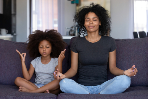 Mother and daughter meditate on couch