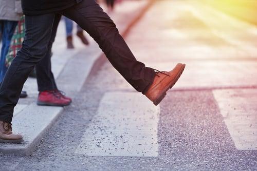 Foot stepping down onto crosswalk