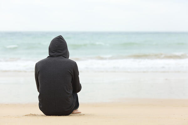 back view of a person sitting alone on beach wearing a dark sweatshirt and jeans, hood pulled up