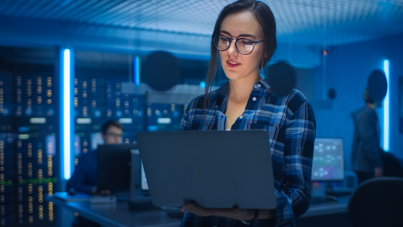 Portrait of a Smart Young Woman Wearing Glasses and holding a Laptop. In the Background Technical Department Office with Specialists Working and Functional Data Server Racks