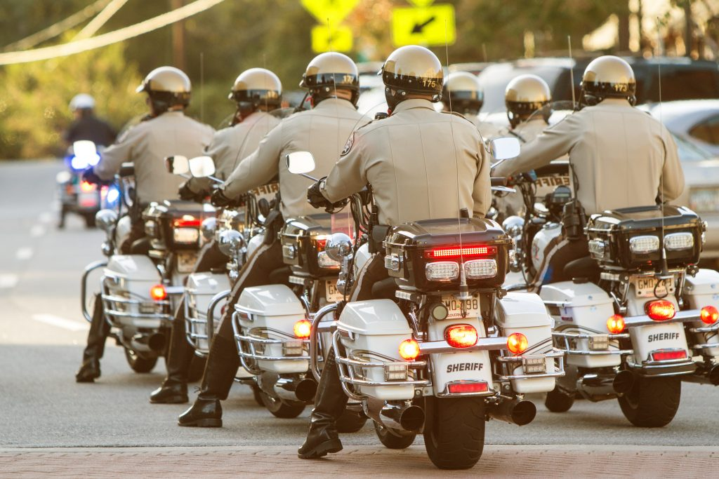 A group of local motorcycle police officers in the Sheriff's Department ride through town in unison.