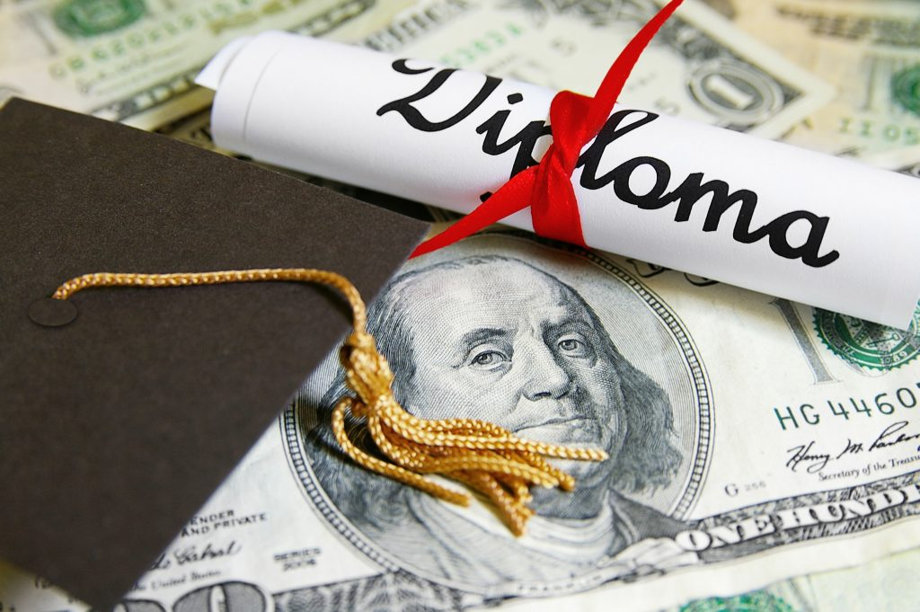 A diploma sits on top of 100 dollar bills and a graduation cap nearby.
