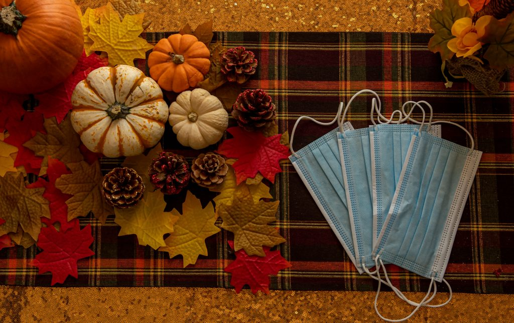 A 2020 thanksgiving table setting, complete with autumnal placemats, colorful gourds, pine cones, and masks.