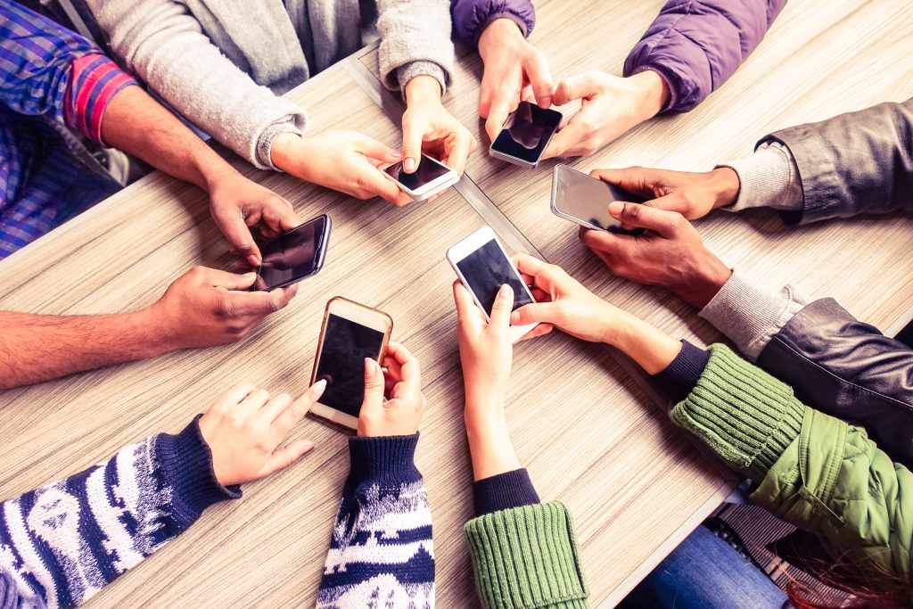 A group of college students in a circle on cell phones